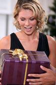 Jeune femme ravi de recevoir un cadeau de noël joliment emballés — Photo