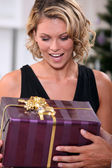 Young woman delighted to receive a prettily wrapped Christmas present — Stock Photo