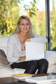 Blond girl sat at home with laptop computer — Stock Photo
