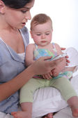 Mother resting baby on knee whilst looking at mobile telephone — Stock Photo