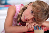 Little girl with crayons resting head on desk — Stock Photo