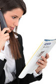 Woman calling an advert in a magazine — Stock Photo
