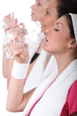Women drinking water after training — Stock Photo