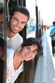 Couple leaning out of a tram door at a station — Stok fotoğraf