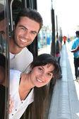 Couple s'appuyant sur une porte de tram à une station — Photo