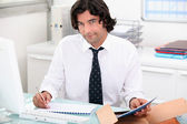 Handsome man doing his paperwork — Stock Photo