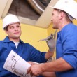 Two workers dressed in blue jumpsuits in a house under construction, one of — Stock Photo