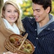 Couple collecting chestnuts in the woods — Stock Photo