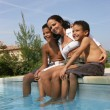 Mother and kids sitting at the poolside — Stock Photo #8402884