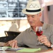 Senior on vacation drinking fresh wine in a restaurant — Stock Photo
