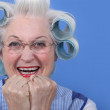 Senior woman with curlers in her hair laughing — Stock Photo #8404358