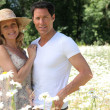 Couple in field of flowers. — Stock Photo