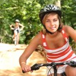 Teenage girls riding bikes through the forest — Stock Photo