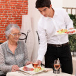 Senior couple being served food in a restaurant — Stock Photo #8407071