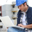 A foreman checking his laptop onsite. - Stock Photo
