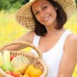 Stock Photo: Womholding basket of fruit and vegetables