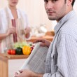 Young woman cooking and boyfriend reading newspaper — Stock Photo