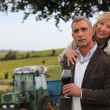 Couple of wine producers in front of vines — Stock Photo