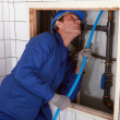 Stock Photo: Plumber feeding blue pipe behind wall