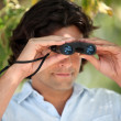 Man looking through a pair of binoculars — Stock Photo