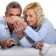 Woman covering her husband's eyes during a scary film — Stock Photo