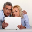 Middle aged couple with a laptop on their bed. — Stock Photo