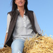 Stock Photo: Womsitting on bale of hay