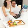 Couple enjoying breakfast in bed — Stock Photo #8409127