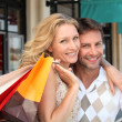 Portrait of a couple with shopping bags - Stock Photo