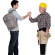 Tradesman making a pact with a young man — Stock Photo #8409304