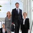 Small group of executives walking up stairs in a glass roofed atrium - Foto Stock