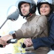 Couple riding a scooter - Stockfoto