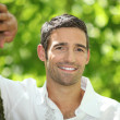 Smiling man leaning against a tree trunk — Stock Photo #8409565