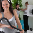 Smiling brown-haired woman on cross trainer — Stock Photo #8409713