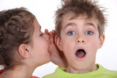 Little girl telling a boy a secret — Stock Photo