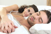 Woman watching her husband sleeping — Stock Photo
