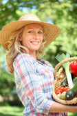 Woman smiling with a straw hat holding basket of vegetables. — Stock Photo