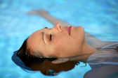 Brunette laying in pool — Stock Photo