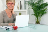 Woman working on her laptop at home — Stock Photo