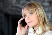 Blond woman making telephone call from home — Stock Photo