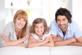 Family laying on bed together — Stock Photo