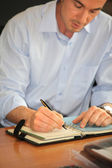 Man writing in a personal organizer — Stock Photo