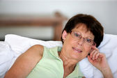 Retired woman propped up against some cushions — Stock Photo