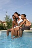 Madre e hijos sentados junto a la piscina — Foto de Stock