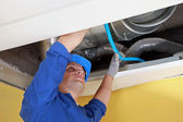 Worker holding blue pipe in place under air ducts — Stock Photo