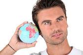 Man listening into a globe — Stock Photo