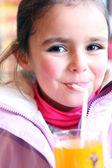 Młoda dziewczyna picie szklanki soku pomarańczowego — Zdjęcie stockowe