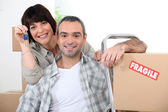 Couple moving into new home with doorkeys and boxes marked fragile — Stock Photo