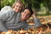 Couple lying in the leaves — Stock Photo