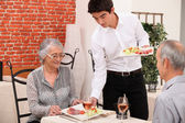 Senior couple being served food in a restaurant — Stock Photo